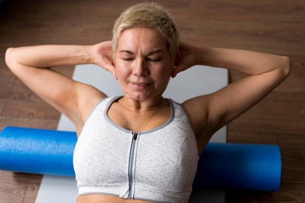 Senior vrouw met kort haar fitness doen