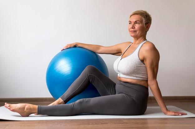 Senior vrouw met kort haar met behulp van een yogamat