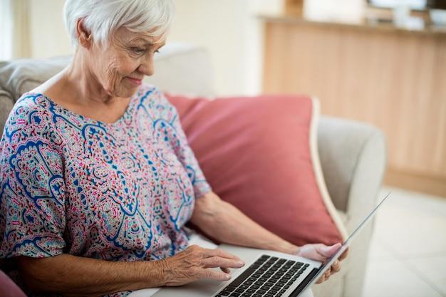 Senior vrouw met laptop in de huiskamer