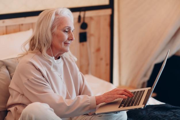 Senior vrouw met laptop ontspannen op glamping camping tent. moderne vakantie levensstijl concept.