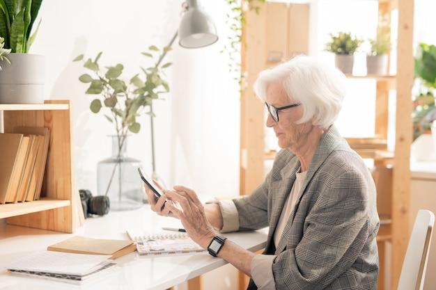 Senior vrouw met mobiele gadget scrollen of berichten tijdens pauze zittend door werkplek op kantoor