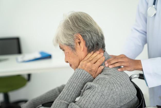 Senior vrouw met nekpijn in het medische kantoor, zieke senior vrouw met nek- en schouderpijn in de rug op het gewricht en de spieren.
