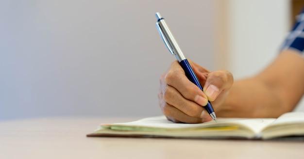 Senior vrouw met pen om te schrijven op notebook dagboek planning over pensioen leven