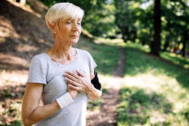 Senior vrouw met pijn op de borst die lijdt aan een hartaanval tijdens het joggen