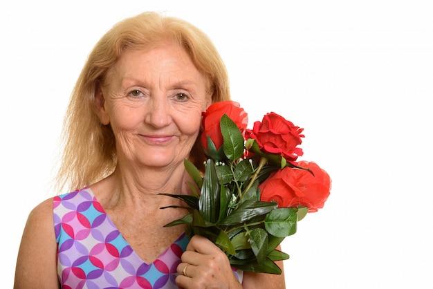 Senior vrouw met rode rozen