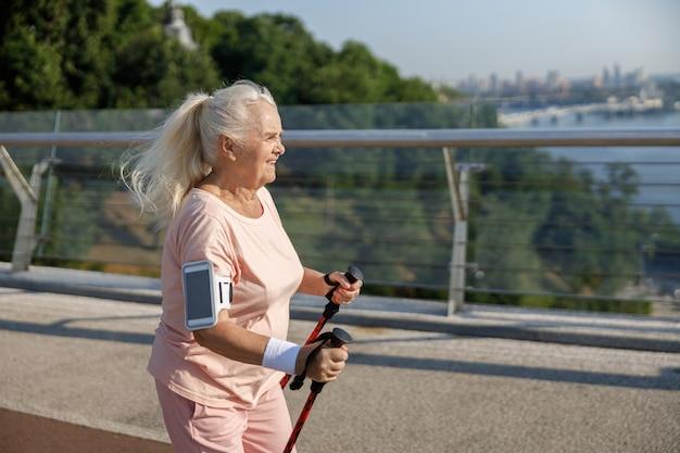 Senior vrouw met smartphone beoefent nordic walking op lege voetgangersbrug