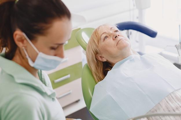 Senior vrouw met tandheelkundige behandeling op het kantoor van de tandarts. de vrouw wordt behandeld voor tanden
