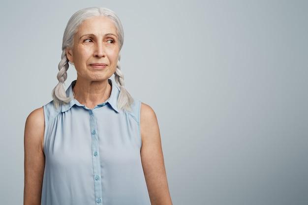 Senior vrouw met vlechten gekleed in blauwe blouse