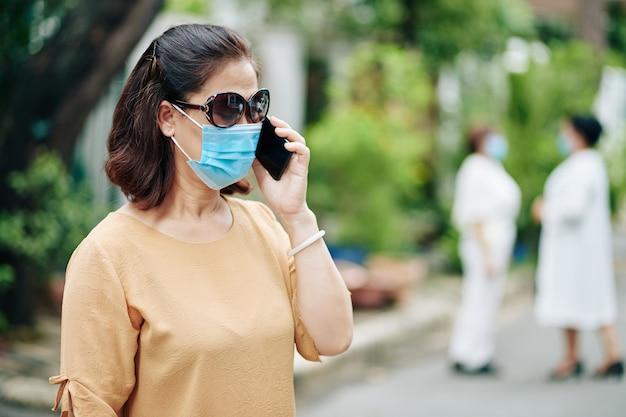 Senior vrouw met zonnebril en medisch masker praten op smartphone met vrienden of familieleden