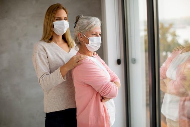 Senior vrouw met zorgzame dochter thuis die medische maskers draagt als bescherming tegen coronavirus