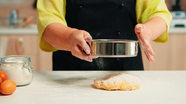 Senior vrouw met zwarte schort zeven bloem op deeg met behulp van metalen zeef gelukkig bejaarde chef-kok met bonete voorbereiding van rauwe ingrediënten voor het bakken van traditioneel brood besprenkelen, zeven in de keuken.