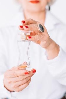 Senior vrouw mode-stijl. parfum trends. fles dure geur in vrouwelijke handen.