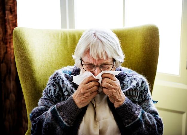 Senior vrouw niezen