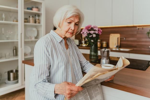 Senior vrouw ontspannen thuis, krant lezen en ontbijten