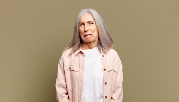 Senior vrouw op zoek goofy en grappig met een dwaze schele uitdrukking, een grapje en gek rond