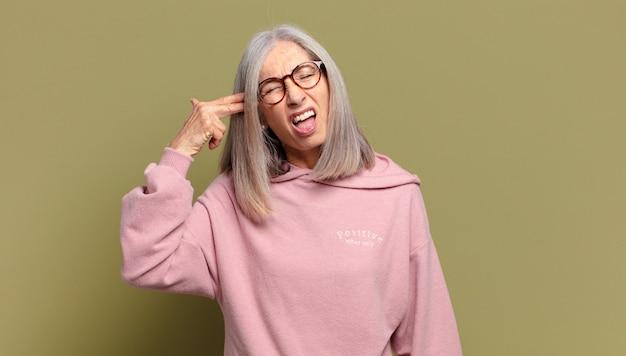 Senior vrouw op zoek ongelukkig en gestrest, zelfmoordgebaar pistool teken met hand, wijzend naar het hoofd