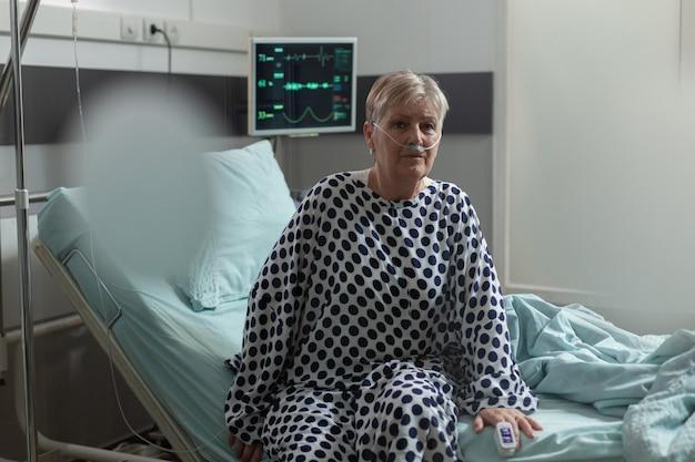 Senior vrouw patiënt zittend op de rand van bed in ziekenhuisbed peinzend kijkend, ademen inademen uitademen met hulp van zuurstofmasker, medicatie ontvangen via een intraveneuze lijn