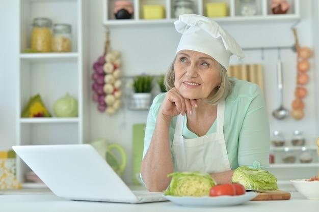 Senior vrouw portret in de keuken met laptop