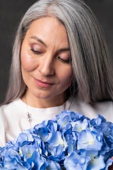 Senior vrouw portret met bloemen boeket