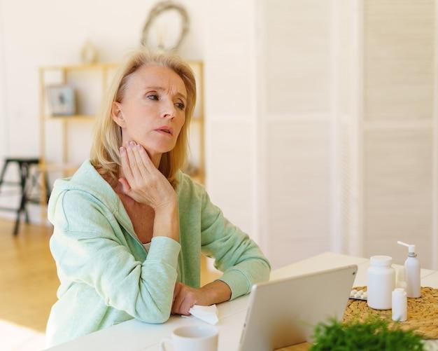 Senior vrouw praat online met dokter over keelpijn schildklier die thuis in de keuken zit