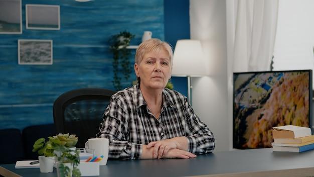Senior vrouw praten en luisteren naar externe collega's tijdens videogesprek