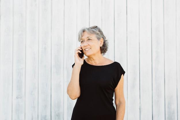 Senior vrouw praten over een telefoon over een witte houten achtergrond