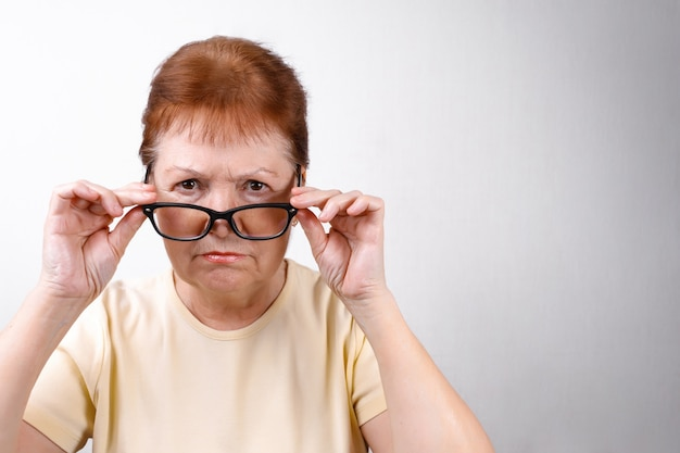 Senior vrouw stijgt bril op wit in een licht t-shirt. plaats voor tekst