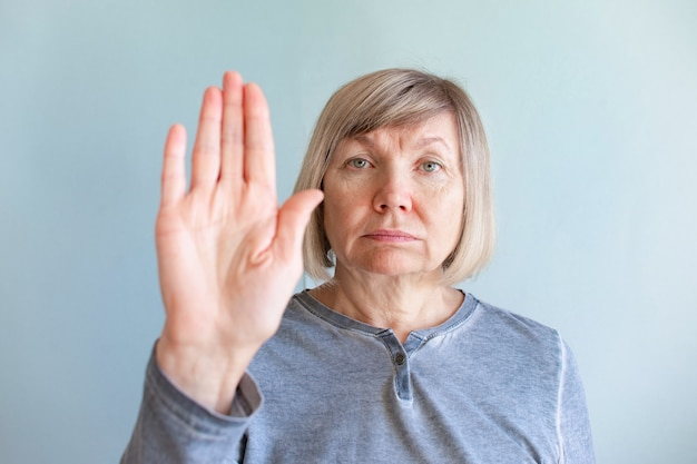 Senior vrouw stress verslaafde en alcoholisme alleen depressie, handen stopbord. hoofdpijn, duizeligheid, migraine. sociale documentaire concepten.