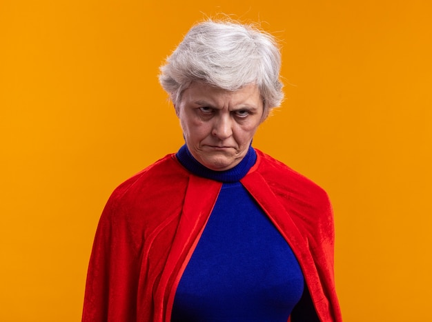 Senior vrouw superheld dragen rode cape camera kijken met boos gezicht fronsen