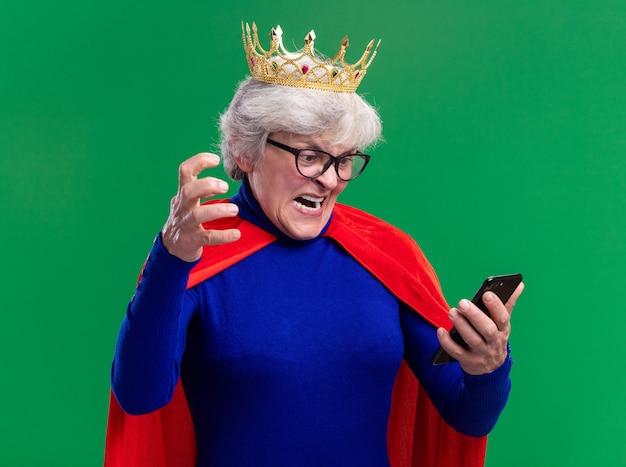 Senior vrouw superheld dragen rode cape en bril met kroon op het hoofd kijken naar het scherm van haar smartphone schreeuwen met agressieve uitdrukking permanent over groene achtergrond