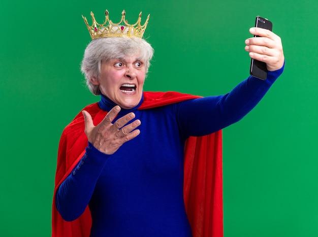 Senior vrouw superheld dragen rode cape en bril met kroon op het hoofd met behulp van smartphone loking op scherm met agressieve uitdrukking schreeuwen staande over groene achtergrond