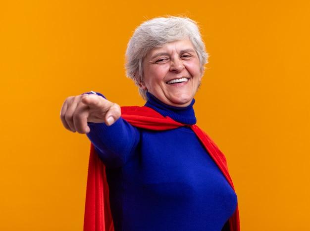 Senior vrouw superheld dragen rode cape kijken camera blij en vrolijk glimlachend