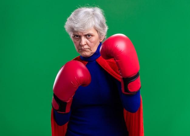 Senior vrouw superheld dragen rode cape met bokshandschoenen kijken naar camera met serieuze zelfverzekerde uitdrukking klaar om te vechten staande over groene achtergrond