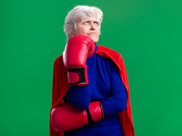 Senior vrouw superheld dragen rode cape met bokshandschoenen opzij kijken