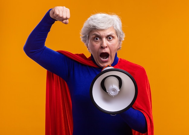 Senior vrouw superheld dragen rode cape schreeuwen naar megafoon met gebalde vuist staande over oranje achtergrond