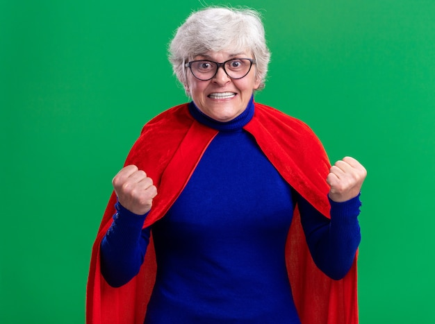 Senior vrouw superheld met rode cape en bril balde vuisten gelukkig