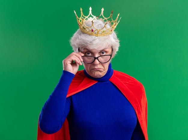 Senior vrouw superheld met rode cape en bril met kroon op het hoofd kijkend naar camera met sceptische uitdrukking staande over groene achtergrond
