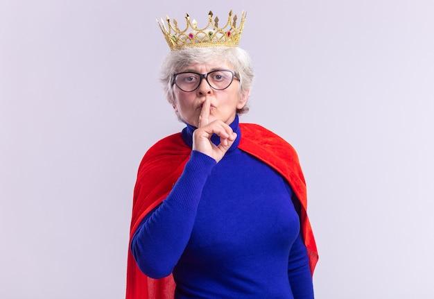 Senior vrouw superheld met rode cape en bril met kroon op het hoofd kijkend naar de camera