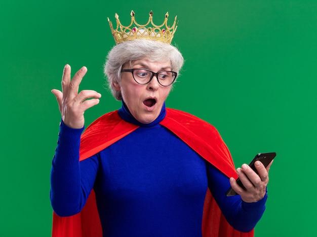Senior vrouw superheld met rode cape en bril met kroon op het hoofd kijkend naar het scherm