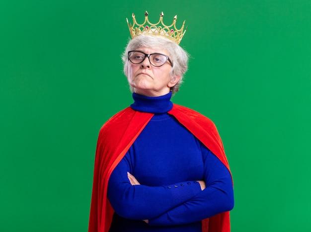 Senior vrouw superheld met rode cape en bril met kroon op het hoofd opzij kijken