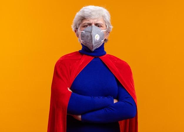 Senior vrouw superheld met rode cape en gezichtsbeschermend masker kijkend naar camera met serieuze zelfverzekerde uitdrukking over oranje achtergrond