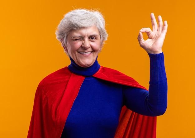 Senior vrouw superheld met rode cape kijkend naar camera glimlachend en knipogend met ok teken staande over oranje achtergrond