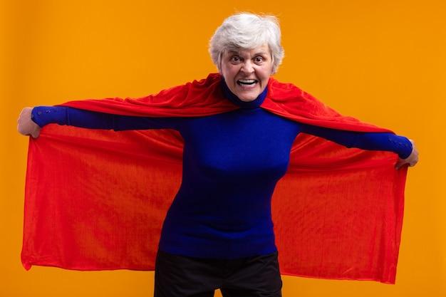 Senior vrouw superheld met rode cape kijkend naar camera met boos gezicht dat haar cape vasthoudt