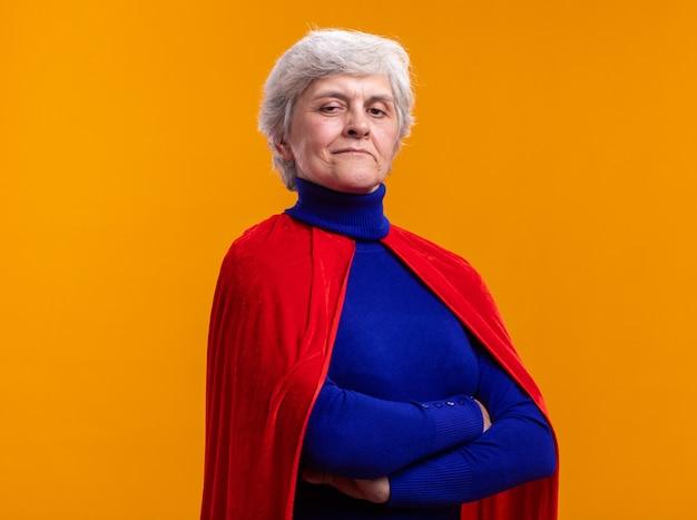 Senior vrouw superheld met rode cape kijkend naar camera met zelfverzekerde uitdrukking met gekruiste armen staande over oranje achtergrond