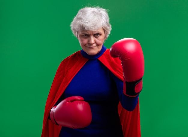 Senior vrouw superheld met rode cape met bokshandschoenen kijkend naar camera met serieuze zelfverzekerde uitdrukking klaar om te vechten
