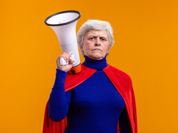Senior vrouw superheld met rode cape met megafoon kijkend naar camera met zelfverzekerde uitdrukking over oranje achtergrond
