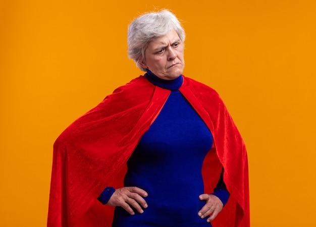 Senior vrouw superheld met rode cape opzij kijkend met een droevige uitdrukking die over een oranje achtergrond staat
