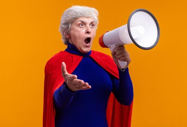 Senior vrouw superheld met rode cape schreeuwend naar megafoon en verward kijkend over oranje achtergrond