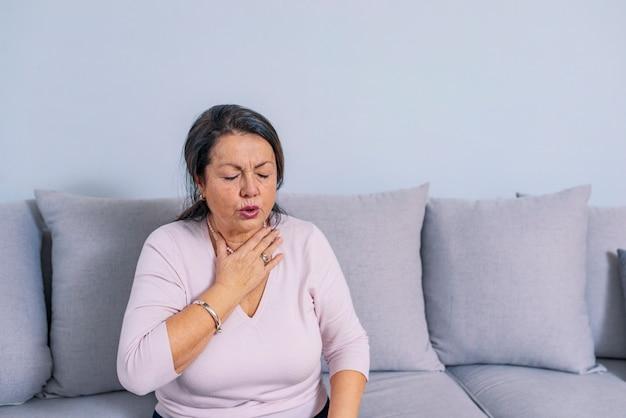 Senior vrouw thuis gevoel onwel. een hogere vrouw die haar hals aanraakt.