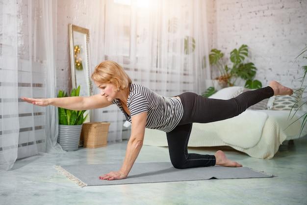 Senior vrouw thuis oefenen, het concept van een gezonde levensstijl, fitness en yoga.